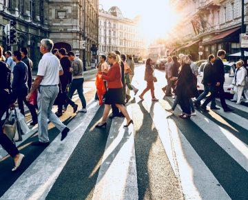 People cross at a busy urban sidewalk