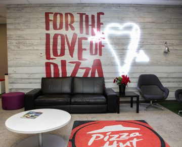 Sitting area with a couch and Pizza Hut Canada carpet